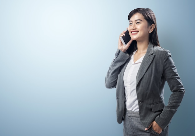 Giovane donna asiatica di affari che parla sullo smartphone Foto Premium