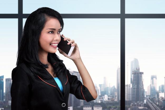 Giovane donna asiatica di affari che per mezzo del telefono cellulare Foto Premium