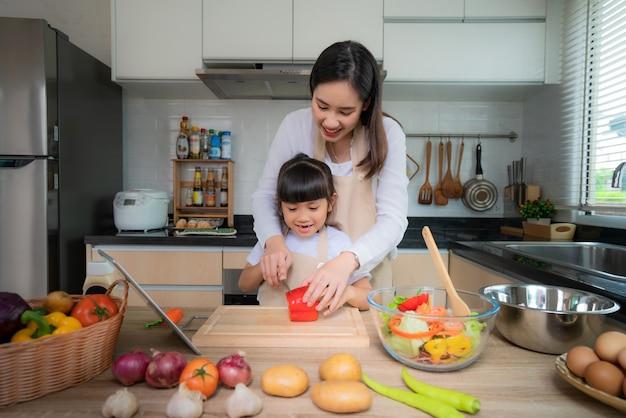 Giovane donna asiatica e sua figlia che cucinano insalata per pranzo. Foto Premium