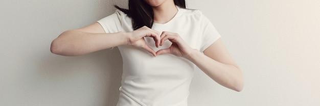Giovane donna asiatica felice che fa le sue mani a forma di cuore Foto Premium