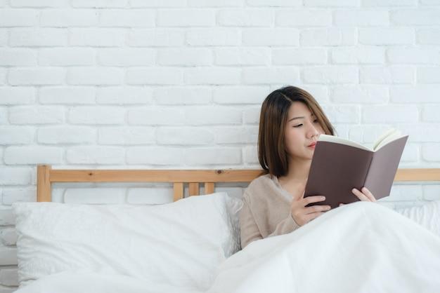 Giovane donna asiatica felice di stile di vita che gode della menzogne sul piacere del libro di lettura del letto in abbigliamento casuale Foto Gratuite