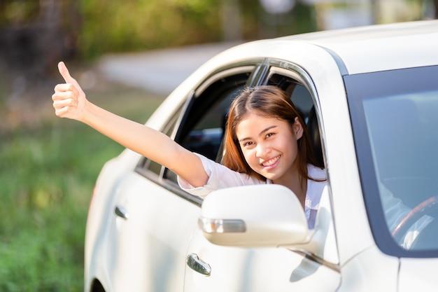 Giovane donna asiatica in camicia bianca alla guida della sua auto e mostrando i pollici Foto Premium