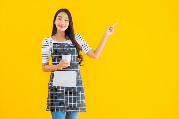 Giovane donna asiatica indossare grembiule con sorriso felice Foto Gratuite