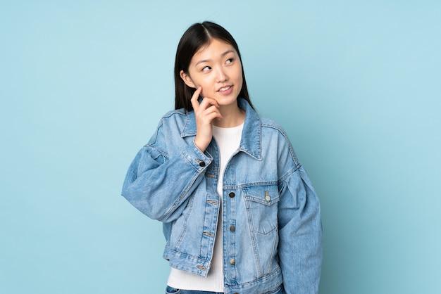 Giovane donna asiatica isolata sulla parete che pensa un'idea mentre osservando in su Foto Premium