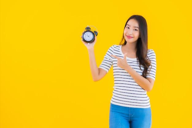 Giovane donna asiatica mostra orologio o sveglia Foto Gratuite