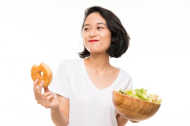 Giovane donna asiatica sopra isolata con insalata e la ciambella Foto Premium