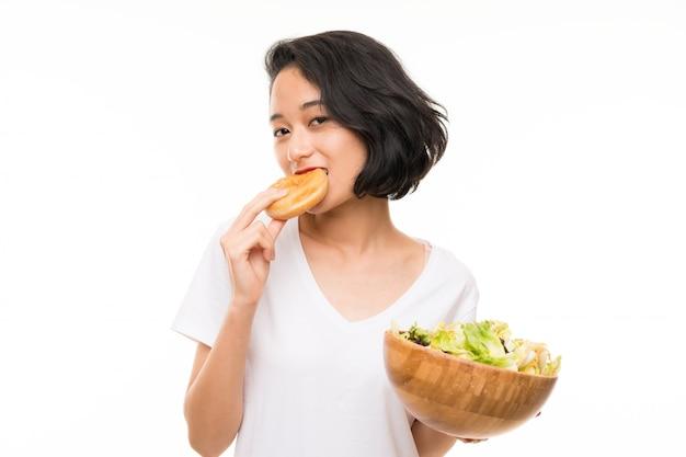 Giovane donna asiatica sopra la parete isolata con insalata e la ciambella Foto Premium