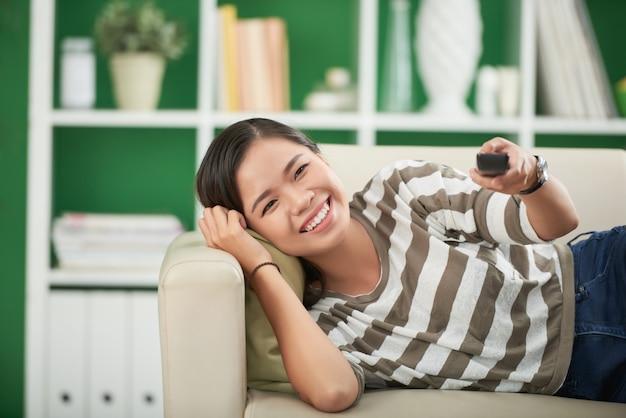 Giovane donna asiatica sorridente che si trova sullo strato a casa, guardando diritto e premendo sul telecomando Foto Gratuite