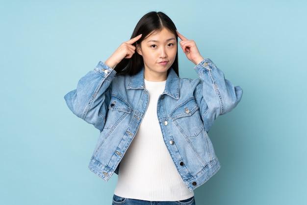 Giovane donna asiatica sulla parete che ha dubbi e pensiero Foto Premium
