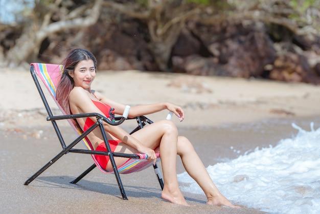 Giovane donna asiatica sveglia in bikini felice sulla bella spiaggia nelle vacanze estive in tailandia Foto Premium