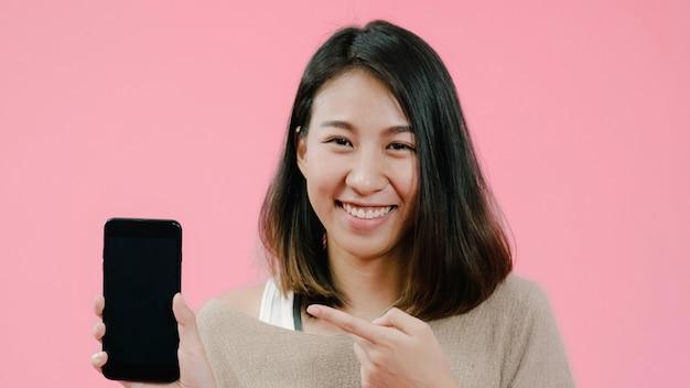 Giovane donna asiatica utilizzando smartphone controllando i social media sensazione sorridendo felice in abbigliamento casual su sfondo rosa Foto Gratuite