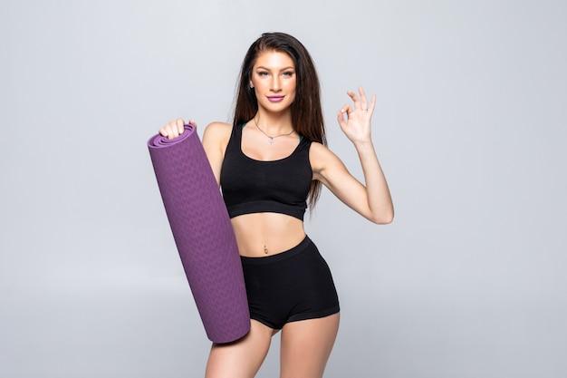 Giovane donna attraente che giudica una stuoia di yoga isolata Foto Gratuite