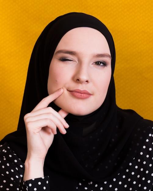 Giovane donna attraente che lampeggia il suo occhio mentre pensava sopra la superficie Foto Gratuite