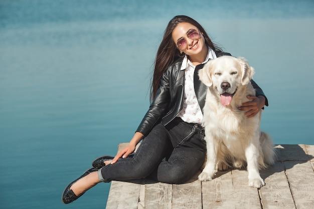 Giovane donna attraente che si siede al molo con il suo cane. migliori amiche all'aperto Foto Premium