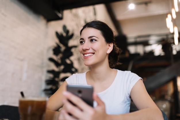 Giovane donna attraente con bel viso e sorriso tenendo il telefono cellulare, scaricare l'applicazione nel bar loft. blogger scrive post sul blog utilizzando smartphone e internet Foto Premium