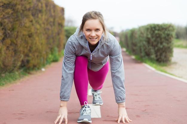 Giovane donna attraente contenta pronta per la corsa all'aperto Foto Gratuite