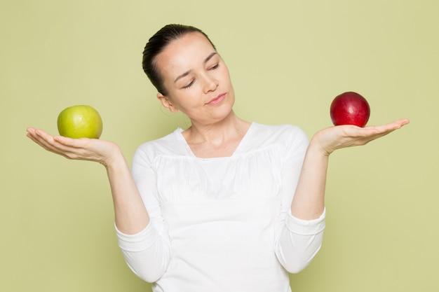 Giovane donna attraente in camicia bianca che tiene le mele verdi e rosse Foto Gratuite