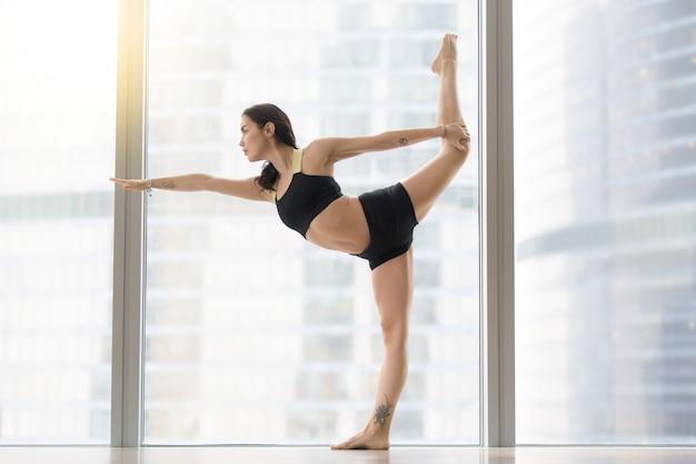 Giovane donna attraente in posa di natarajasana contro la finestra del pavimento Foto Gratuite
