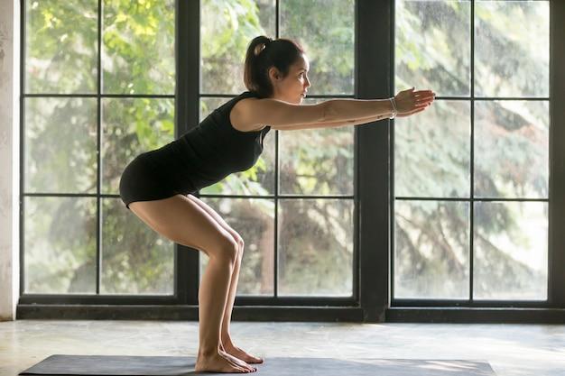 Giovane donna attraente in posa utkatasana, sfondo studio Foto Gratuite