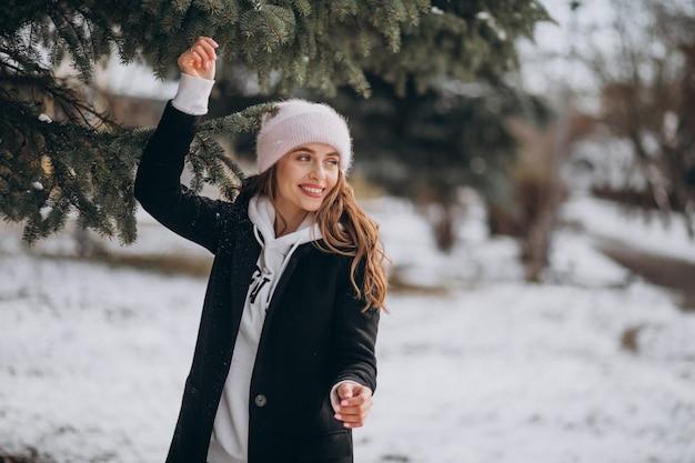 Giovane donna attraente in un parco d'inverno in un cappello carino Foto Gratuite