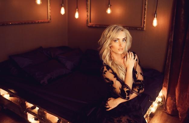 Giovane donna attraente in veste da camera nero che posa sul letto Foto Premium