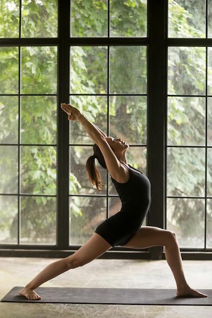 Giovane donna attraente in warrior un esercizio Foto Gratuite
