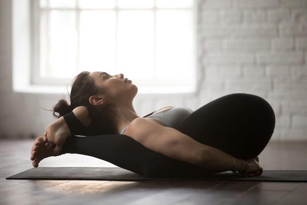 Giovane donna attraente nella posa di sonno di yoga Foto Gratuite