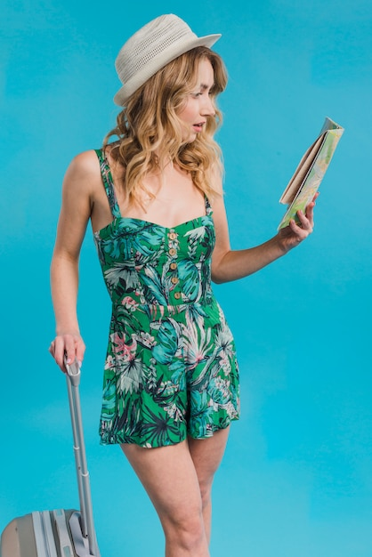 Giovane donna attraente stupita in vestito e cappello che tiene mappa e valigia Foto Gratuite