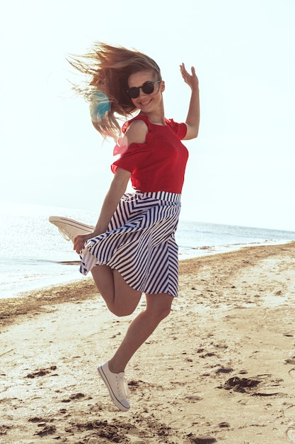 Giovane donna attraente sulla spiaggia dell'oceano al tramonto Foto Premium