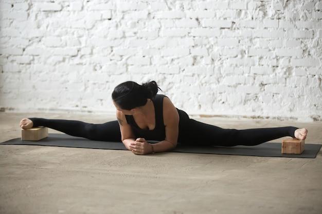 Giovane donna attraente yogi in avanzata samakonasana posa con b Foto Gratuite