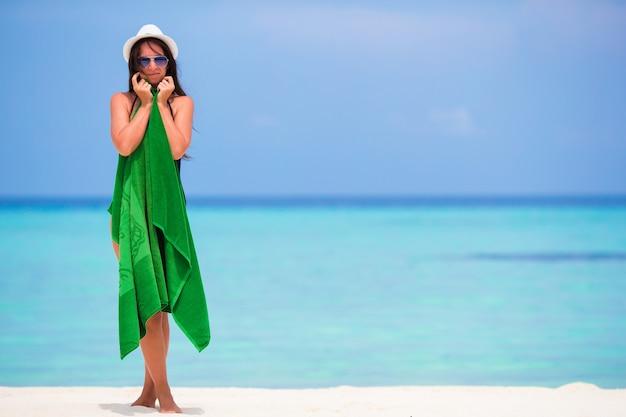 Giovane donna avvolta in un asciugamano sulla spiaggia di sabbia bianca Foto Premium