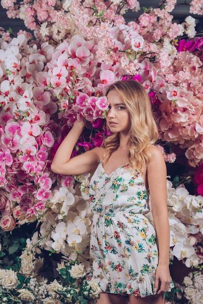 Giovane donna bionda che copre i suoi occhi uno con l'orchidea rosa Foto Gratuite