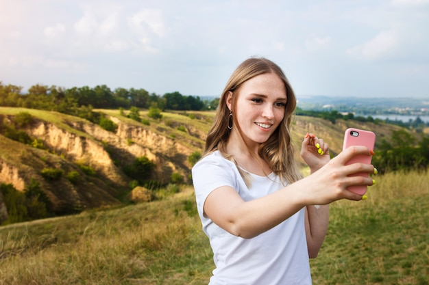 Giovane donna bionda che gode della natura che fa i selfie sul canyon. blog Foto Premium