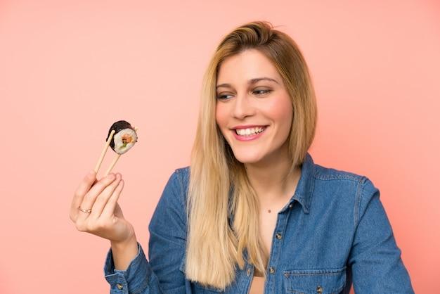 Giovane donna bionda che mangia i sushi Foto Premium