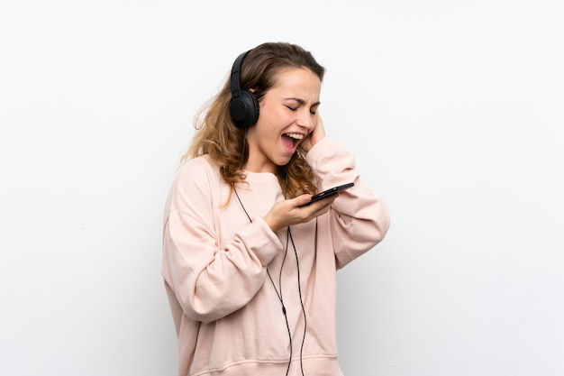 Giovane donna bionda che per mezzo del cellulare con le cuffie e cantare Foto Premium
