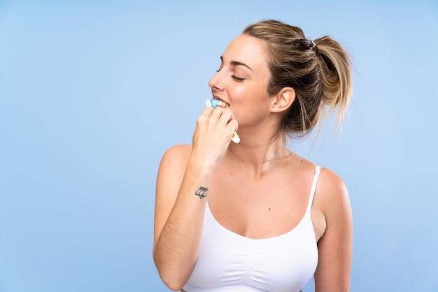 Giovane donna bionda che pulisce i suoi denti Foto Premium