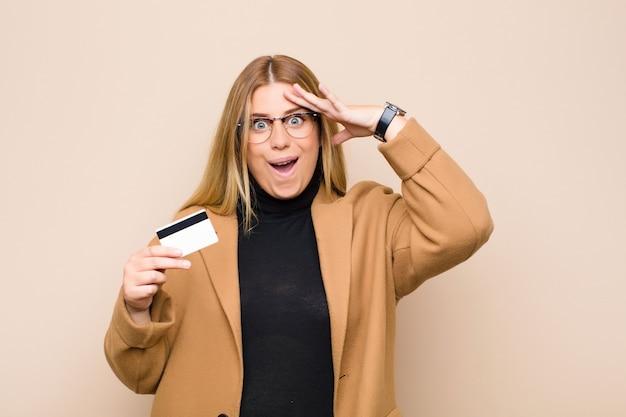 Giovane donna bionda che sembra felice, stupita e sorpresa, sorridente e realizzando sorprendenti e incredibili buone notizie con una carta di credito Foto Premium