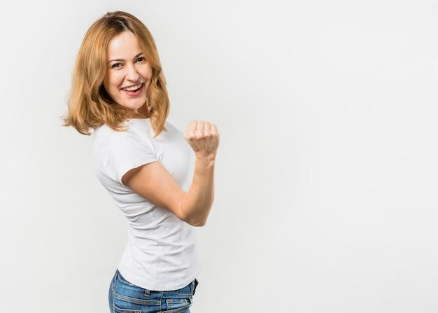 Giovane donna bionda che serra il suo pugno che si leva in piedi contro la priorità bassa bianca Foto Gratuite
