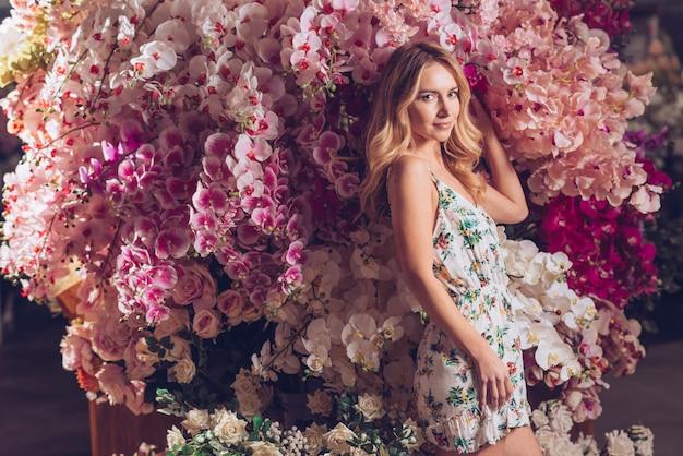 Giovane donna bionda che sta davanti ai fiori variopinti variopinti delle orchidee Foto Gratuite