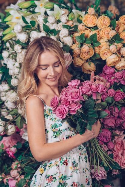 Giovane donna bionda che tiene le rose rosa a disposizione che stanno davanti al contesto del fiore Foto Gratuite