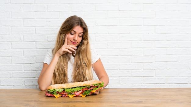 Giovane donna bionda che tiene un grande panino Foto Premium