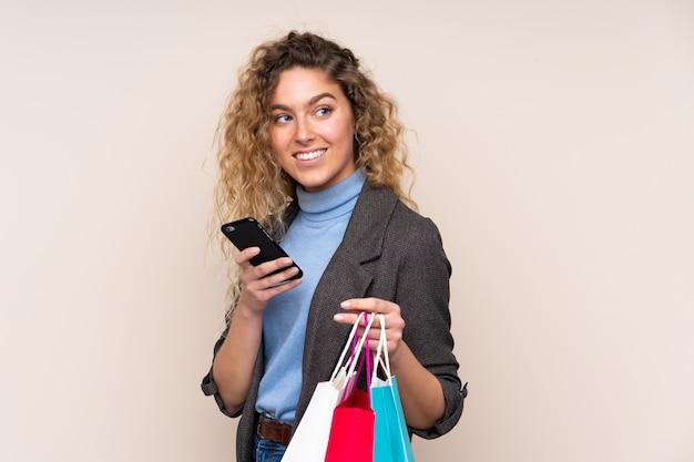 Giovane donna bionda con capelli ricci sui sacchetti della spesa beige della tenuta della parete e un telefono cellulare Foto Premium