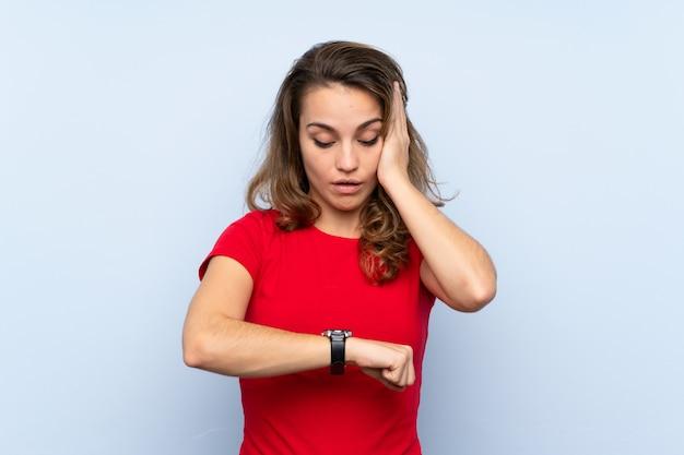 Giovane donna bionda con orologio da polso e sorpreso Foto Premium