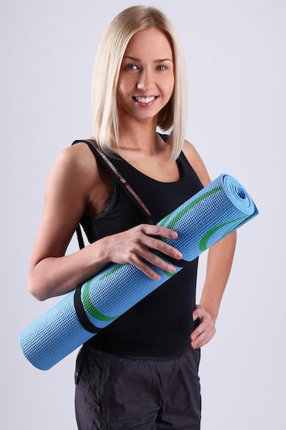 Giovane donna bionda con stuoia di yoga. Foto Gratuite