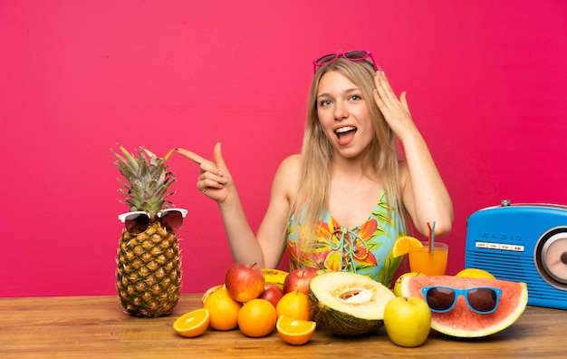 Giovane donna bionda con un sacco di frutta sorpreso e puntando il dito verso il lato Foto Premium