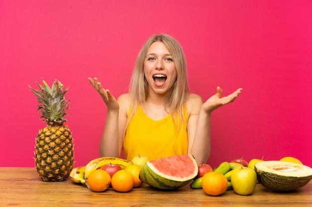 Giovane donna bionda con un sacco di frutti infelici e frustrati con qualcosa Foto Premium