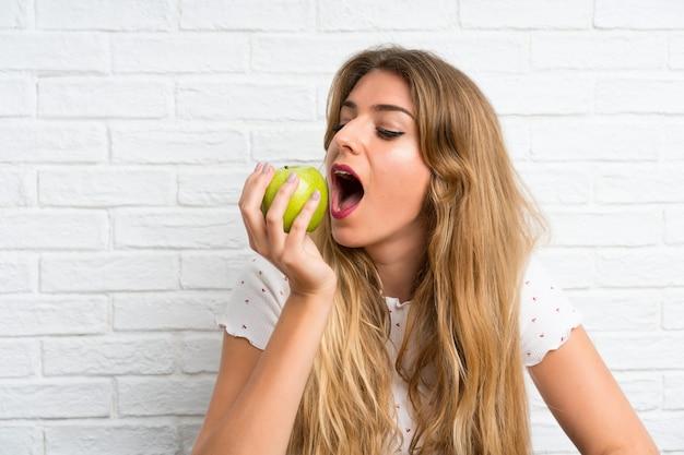 Giovane donna bionda con una mela Foto Premium
