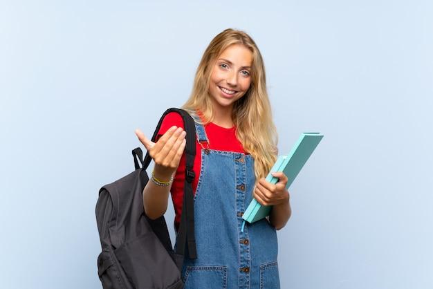 Giovane donna bionda dello studente sopra la parete blu isolata che invita a venire Foto Premium
