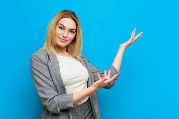Giovane donna bionda graziosa che sorride con orgoglio e con fiducia, sentendosi felice e soddisfatto e mostrando un concetto sullo spazio della copia contro la parete piana Foto Premium