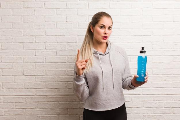 Giovane donna bionda in palestra in possesso di una bottiglia di bevanda isotonica Foto Premium